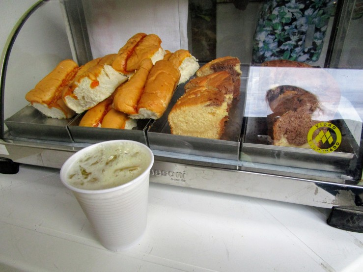 A styrofoam cup filled with caldo de cana, sugarcane juice. In front of a display of bread, as at a bakery.