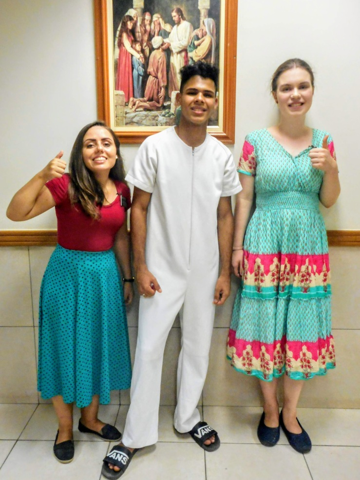 """Sister Porcote, """"Rafael,"""" and sister Faulconer. The two sisters, each on one side of Rafael, are showing their thumbs up signs. Rafael is dressed in white baptismal clothing. The sisters are each wearing their church dresses."""