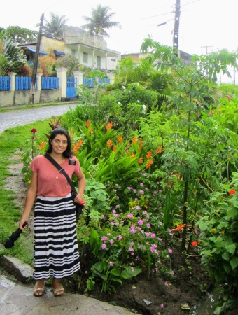 Sister Arece standing outside near the street in front of lush tropical foliage and flowers.