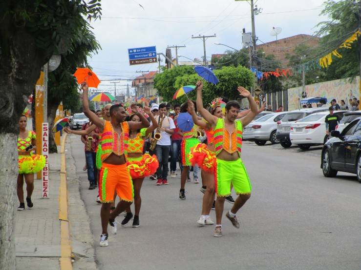 Frevo dancers holding little umbrellas and dressed in orange green and yellow neon clothing for Carnaval in Brazil