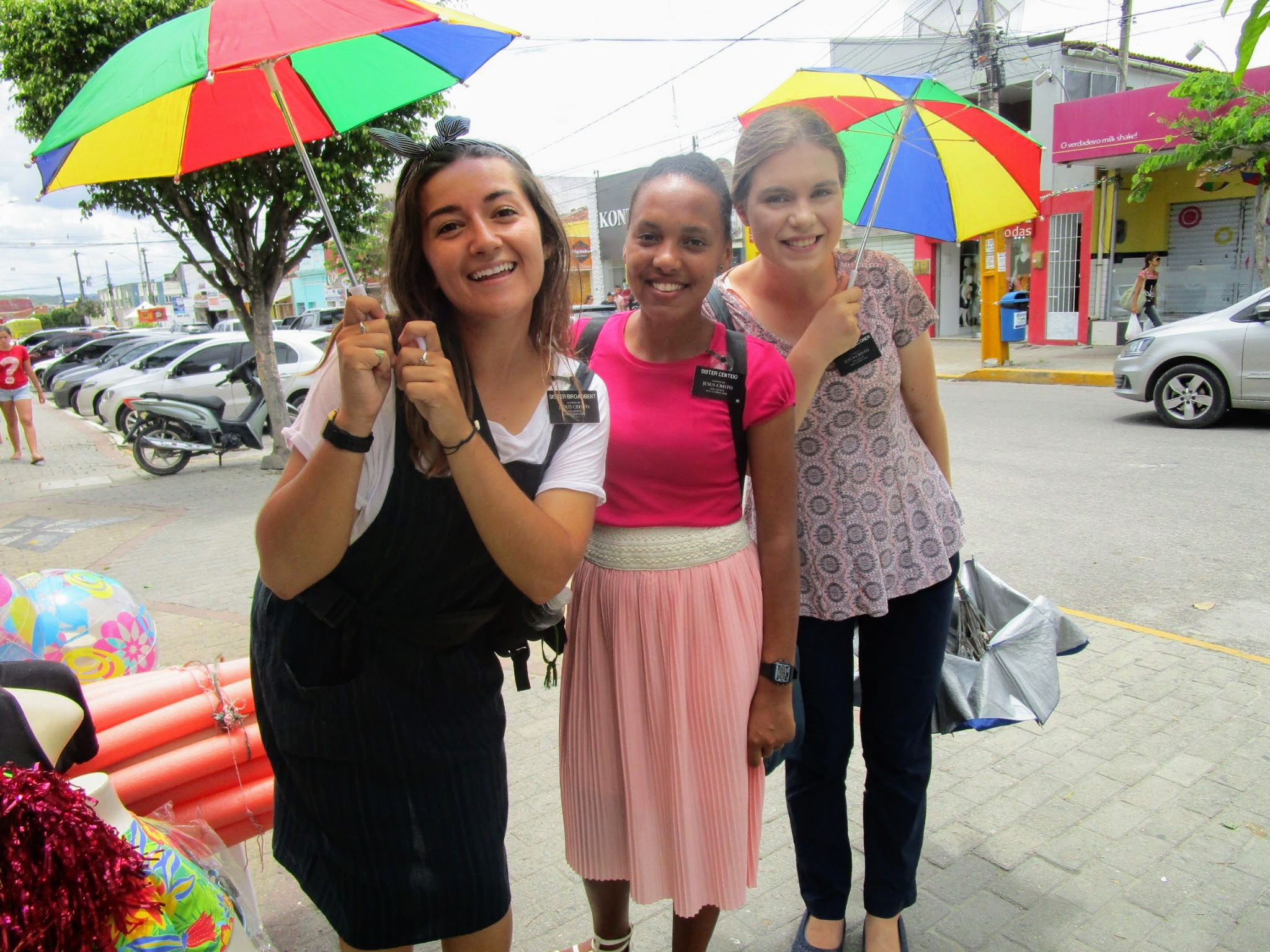 Sister Broadbent, Sister Centeio, and Sister Faulconer, Missionaries for the Church of Jesus Christ of Latter-day Saints holding small frevo umbrellas in Brazil